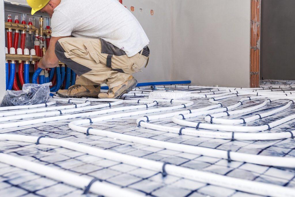 Worker installing a floor radiant heater