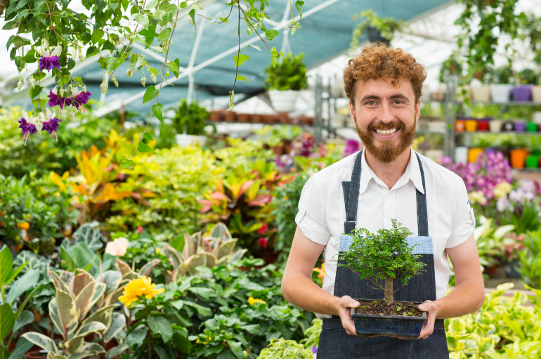 Man holding a plant in a greenhouse