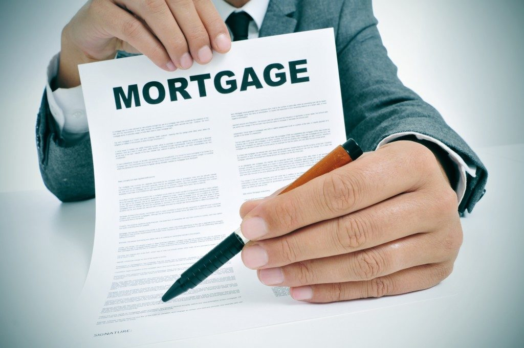 man wearing a suit sitting in a table showing a mortgage loan contract