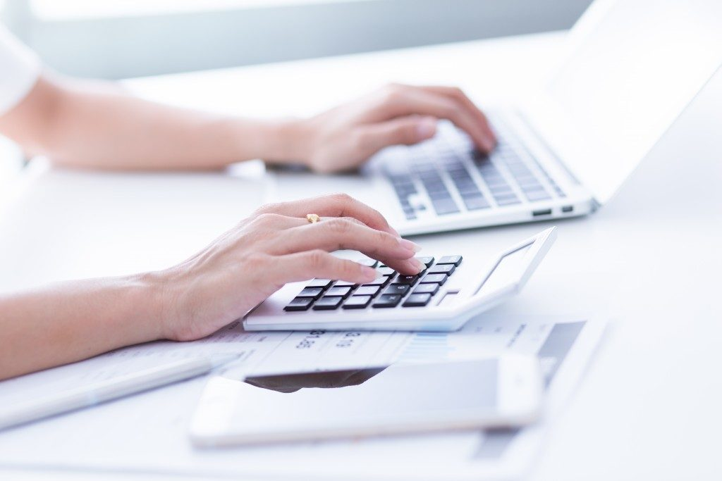 Woman using laptop and calculator