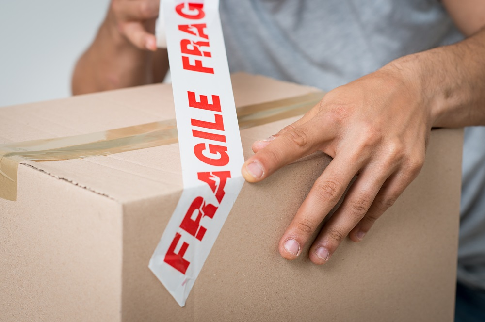 Man putting fragile tape on box