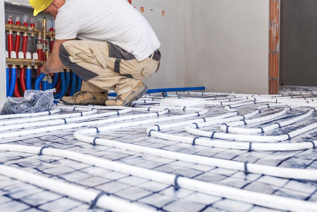 Worker installing a floor heating system