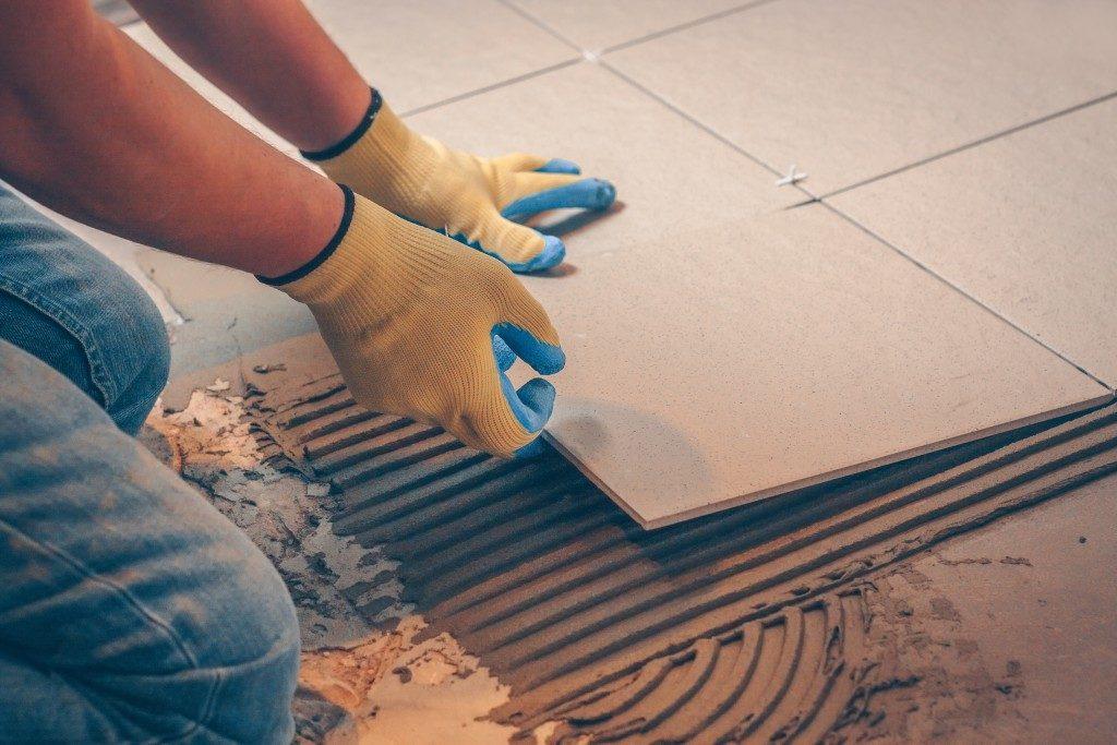 man putting new tiles