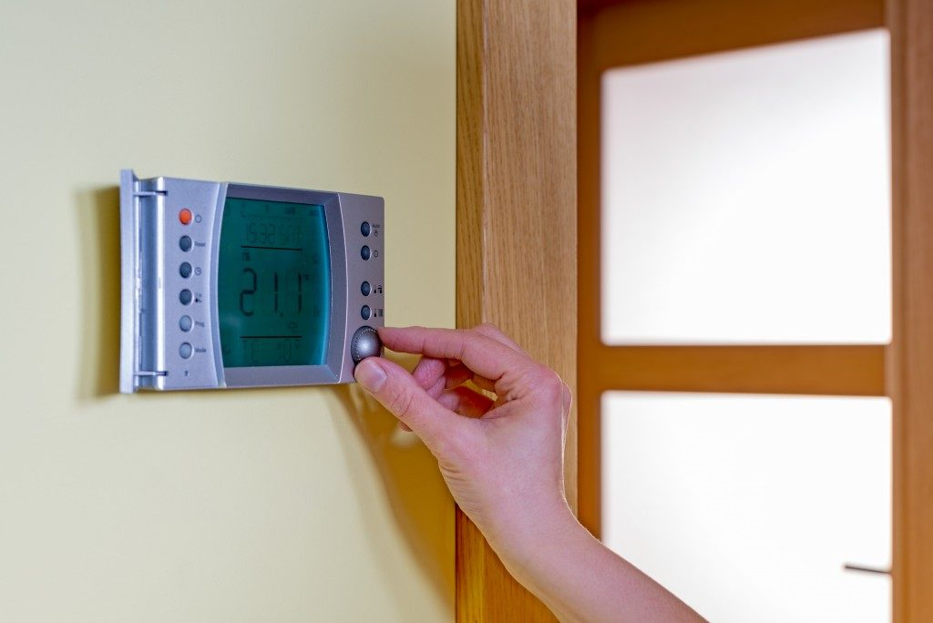 person adjusting temparature using thermostat