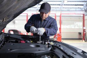 mechanic checking engine of car