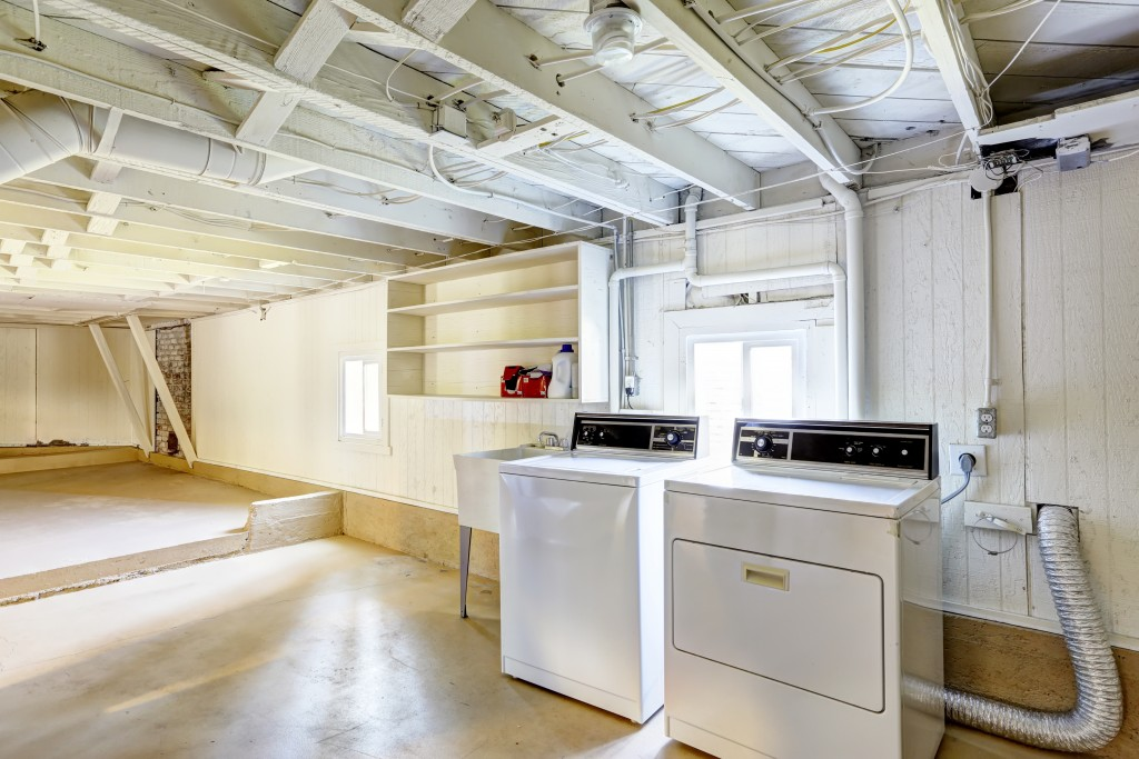 Spacious empty basement with laundry