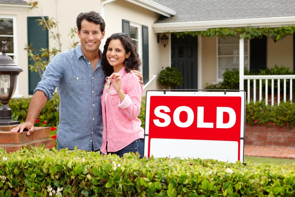 Couple in front of their newly bought house