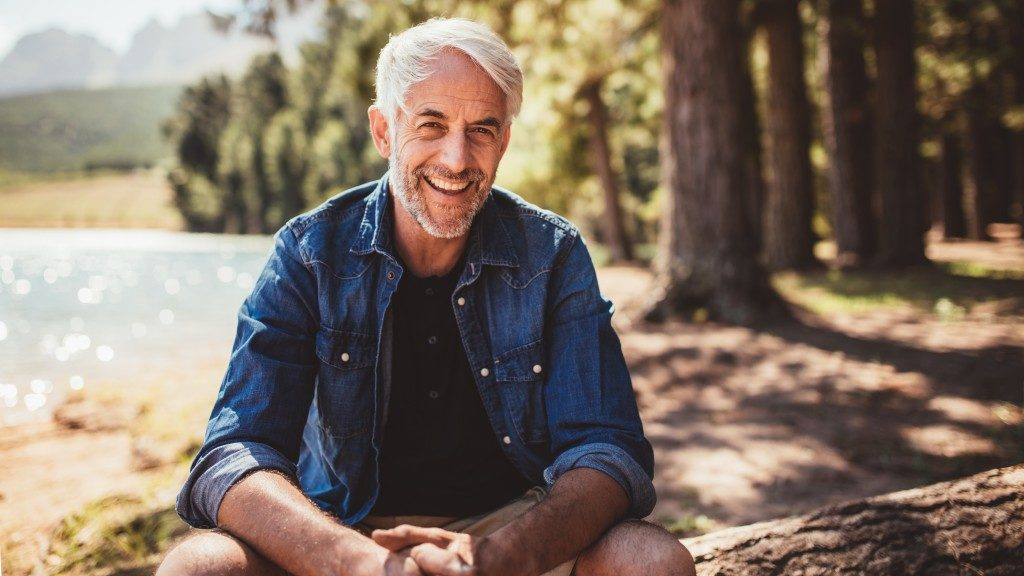 Mature man smiling while sitting beside the lake