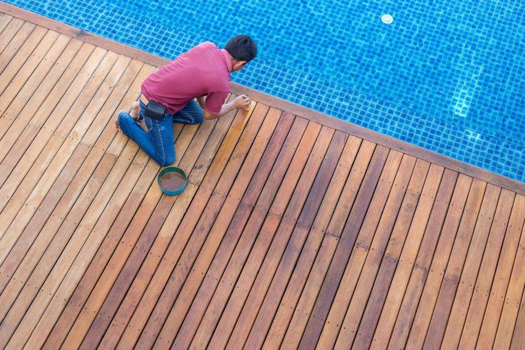 man cleaning the deck floor beside the pool