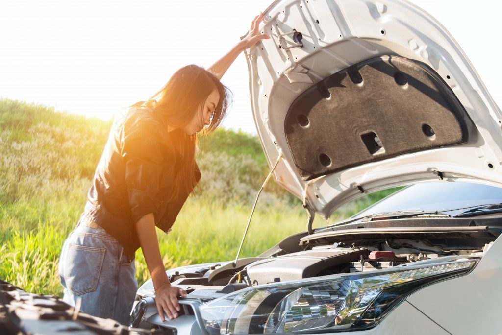 car checking the engine of her car