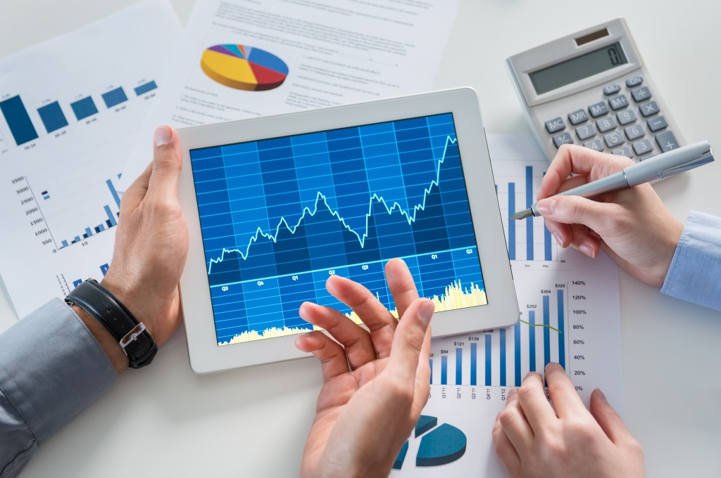 graphs and financial reports discussed with tablet