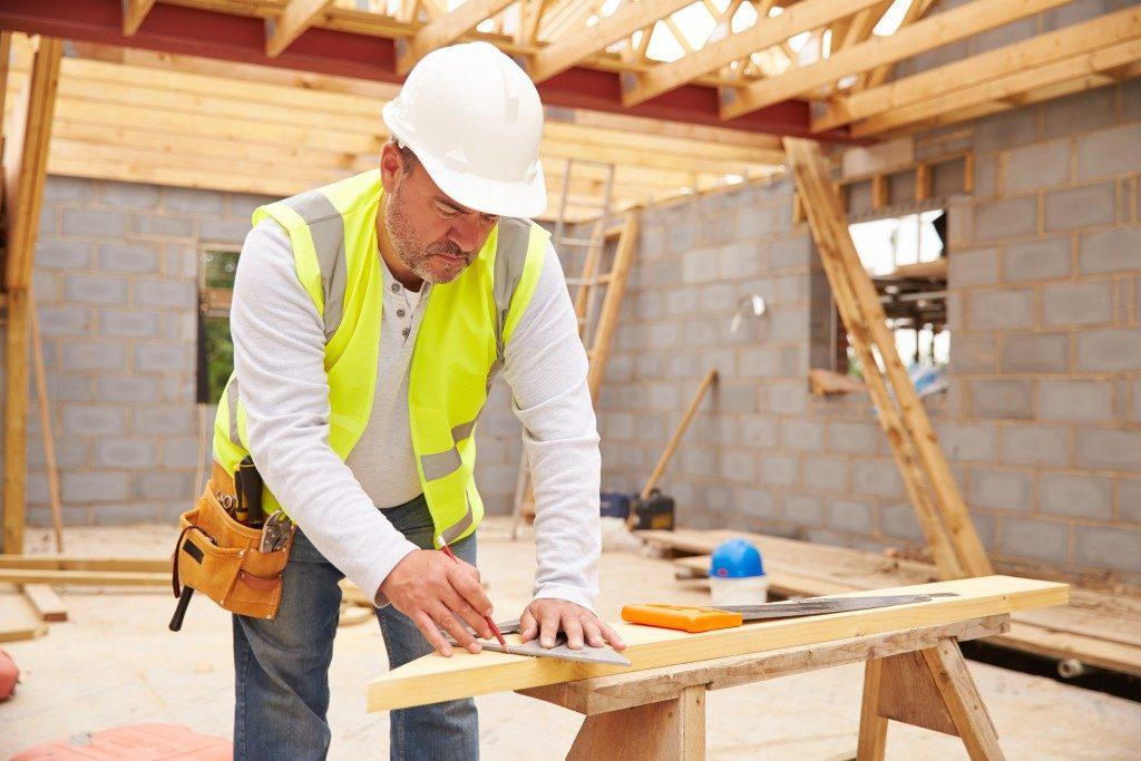 carpenter working inside unfinished home
