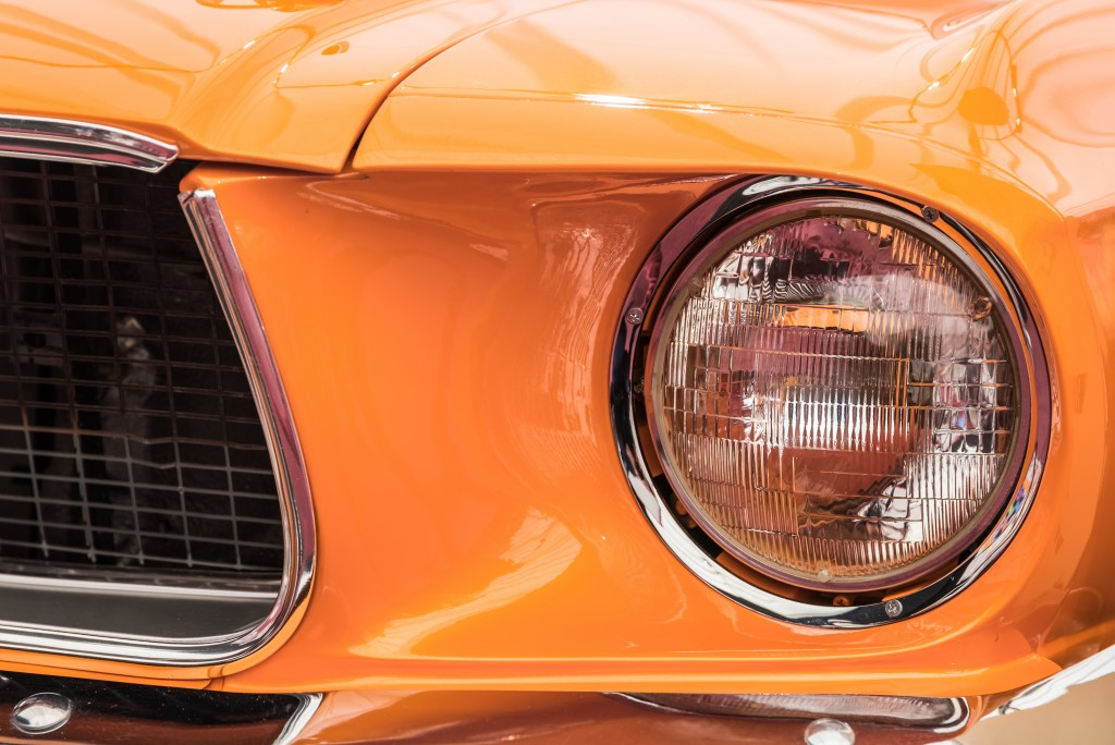 Shiny orange car closeup on headlight