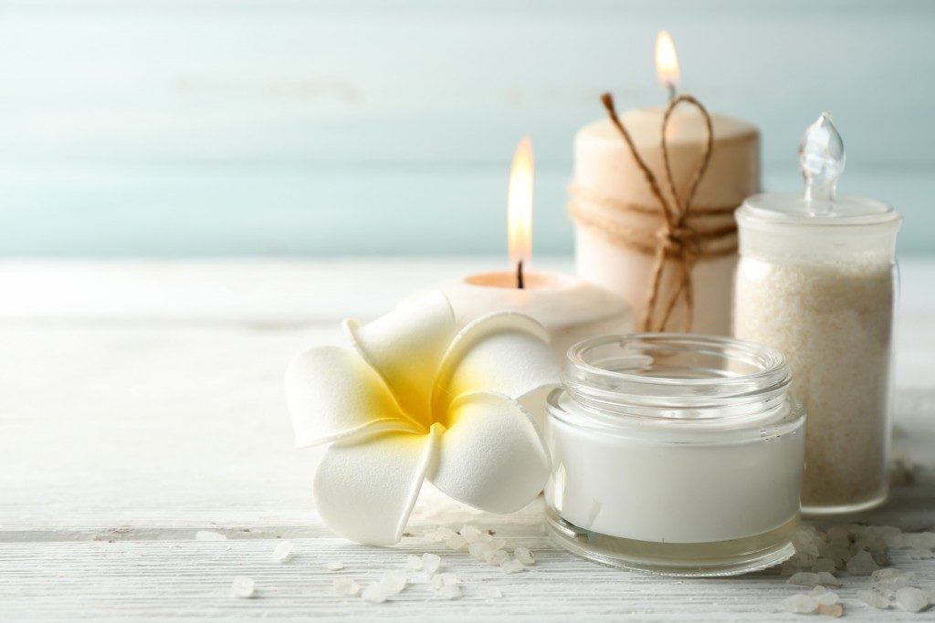 bath and spa products with candles and a flower