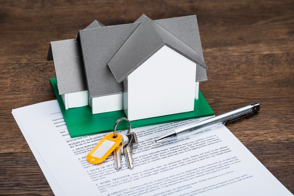 house model with keys, contract, and pen
