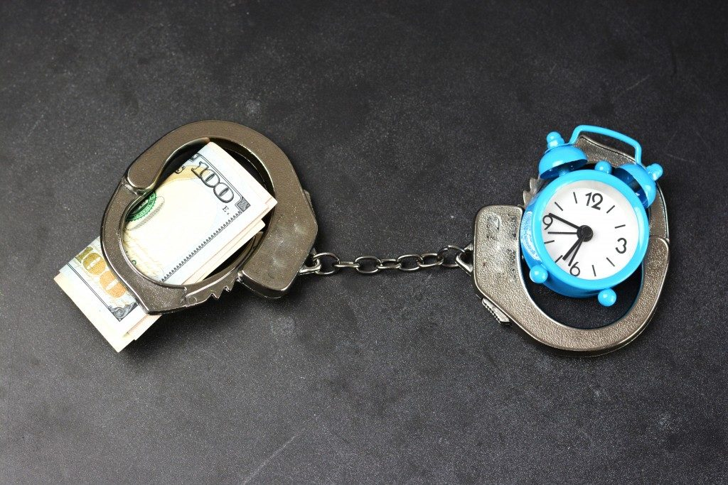 bail concept, money and clock on handcuffs