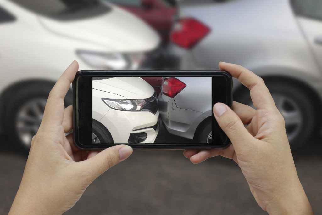 person taking a photo of a road accident