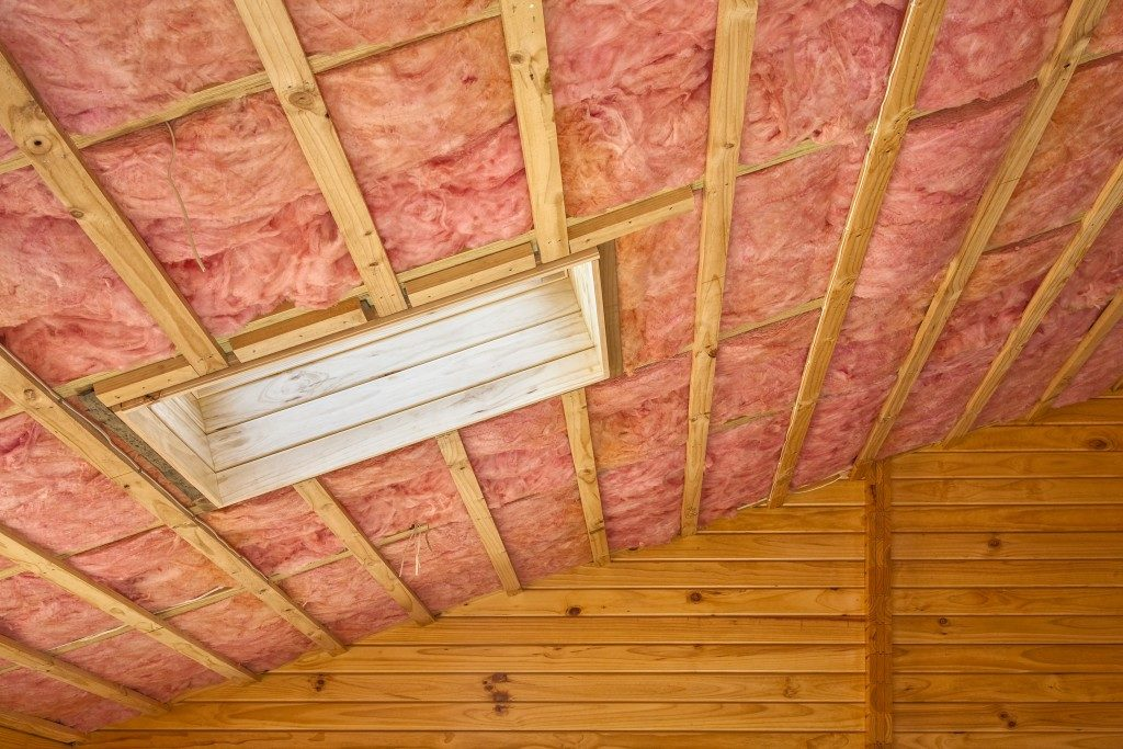 Fibreglass insulation installed in the sloping ceiling of a timber house