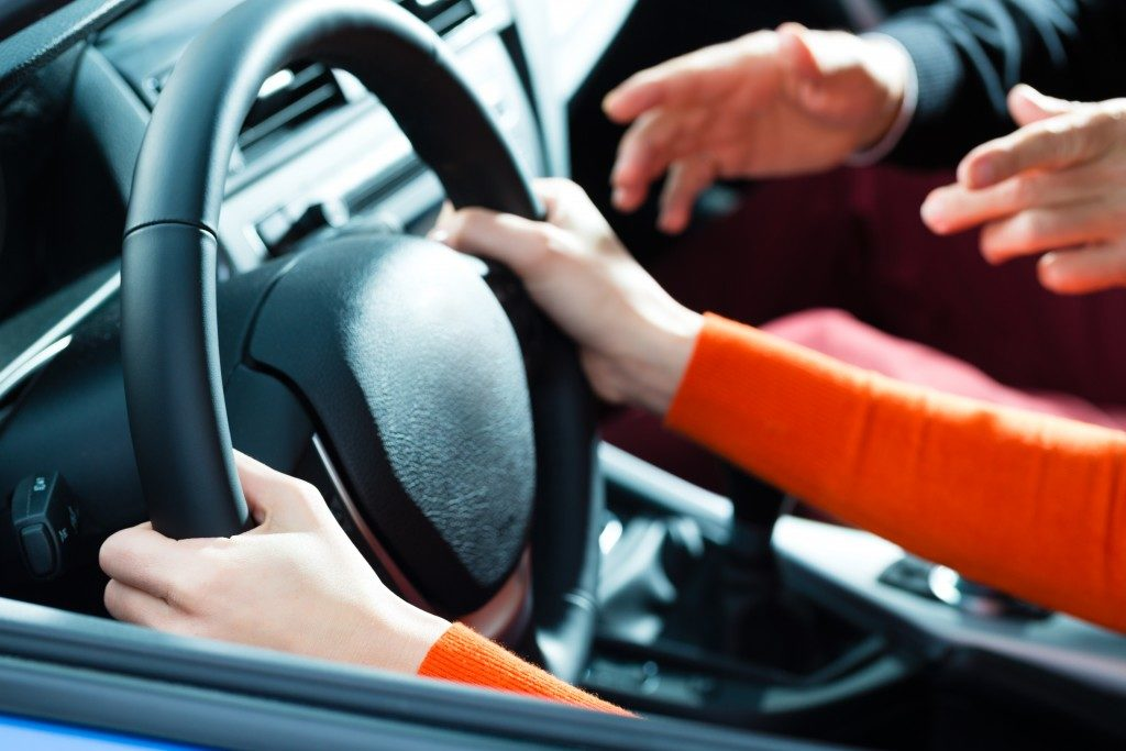Young woman steer a car with the steering wheel