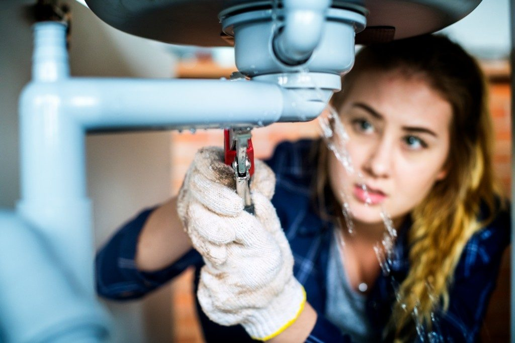 Female plumber fixing pipe