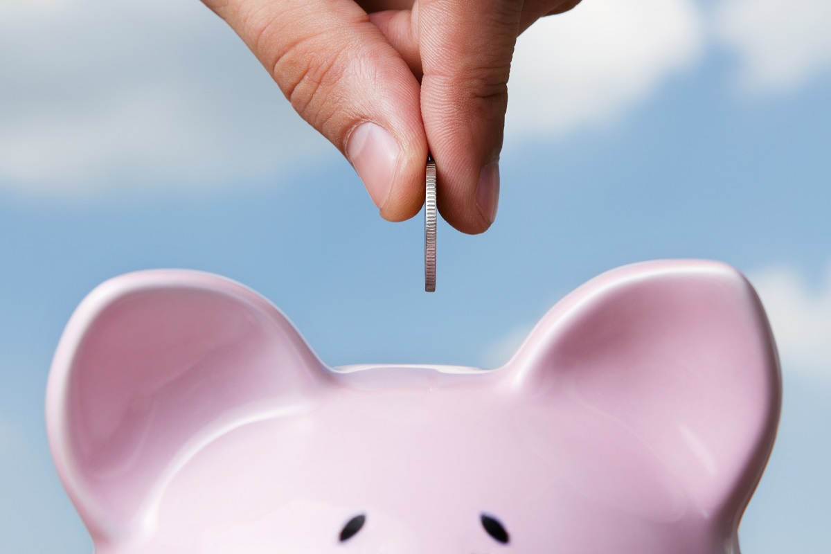 coin being placed in a piggy bank
