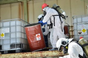 Professionals wearing safety gear while handling hazardous chemicals