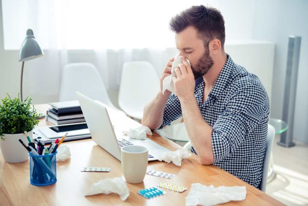 Man sneezing at his desk