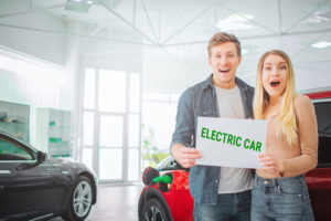 Couple holding electric vehicle sign