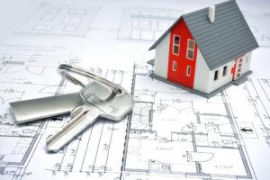 house keys and miniature over a blueprint