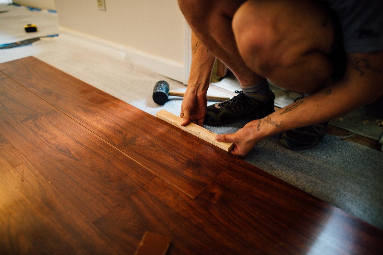 man measuring hardwood flooring