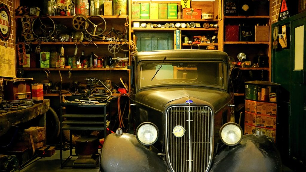 inside of garage with classic car with spare parts and tools behind