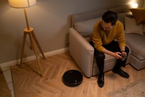 man sitting on couch looking at robot vacuum cleaner