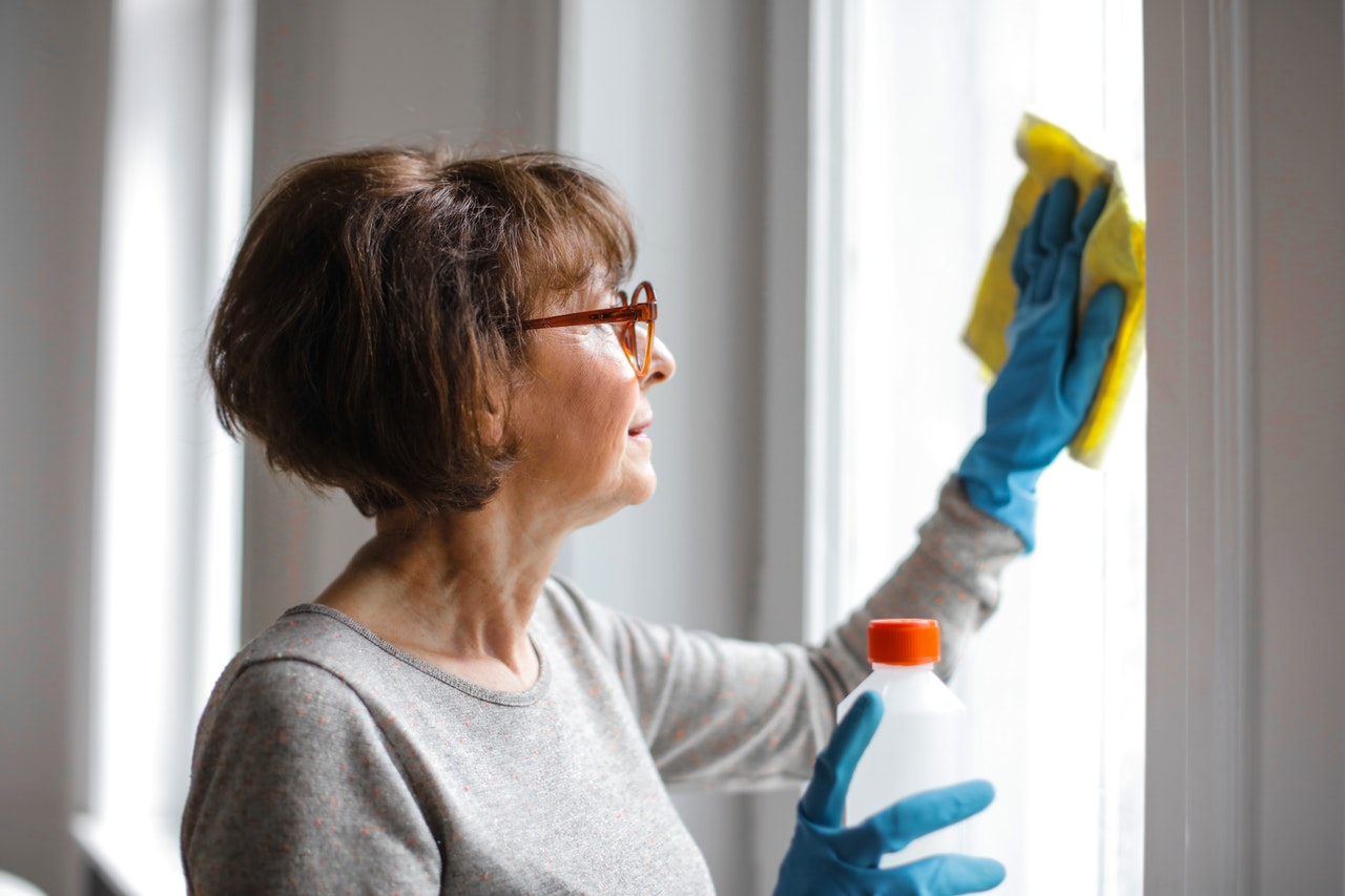 woman cleaning a window pane