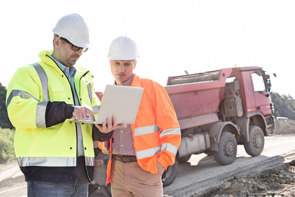 two construction workers on their laptop