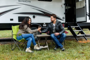 man and woman next to an RV